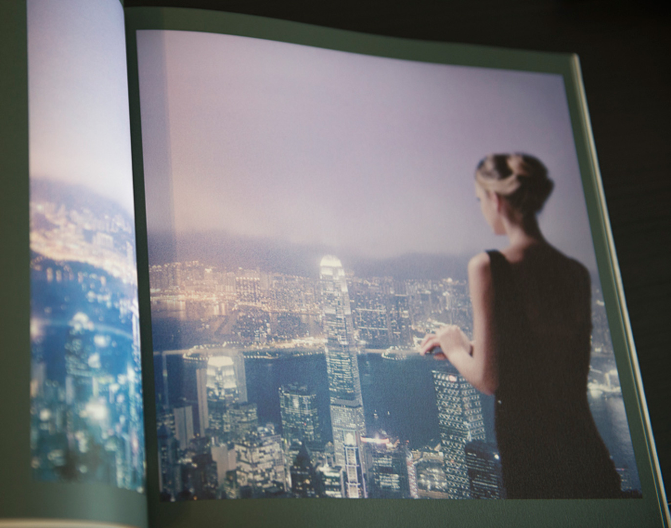 A woman in a low cut back dress looks towards the Hong Kong and Kowloon skyline at night.