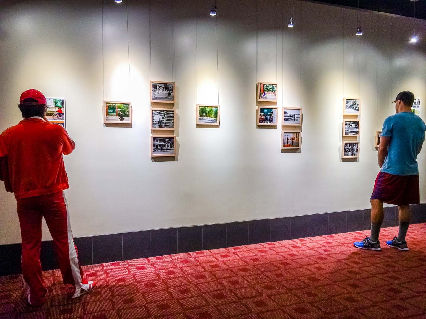 A man in a red track suit reads the artist statement at a photography exhibition while another man in sportswear looks closely at a photograph inside the ArcLight Culver City movie theatre.