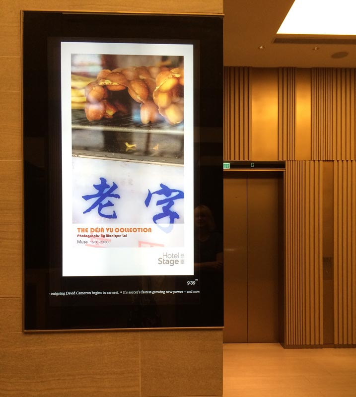 The 'Déjà Vu' photography exhibition is advertised on the digital screen in the lobby of Hotel Stage.
