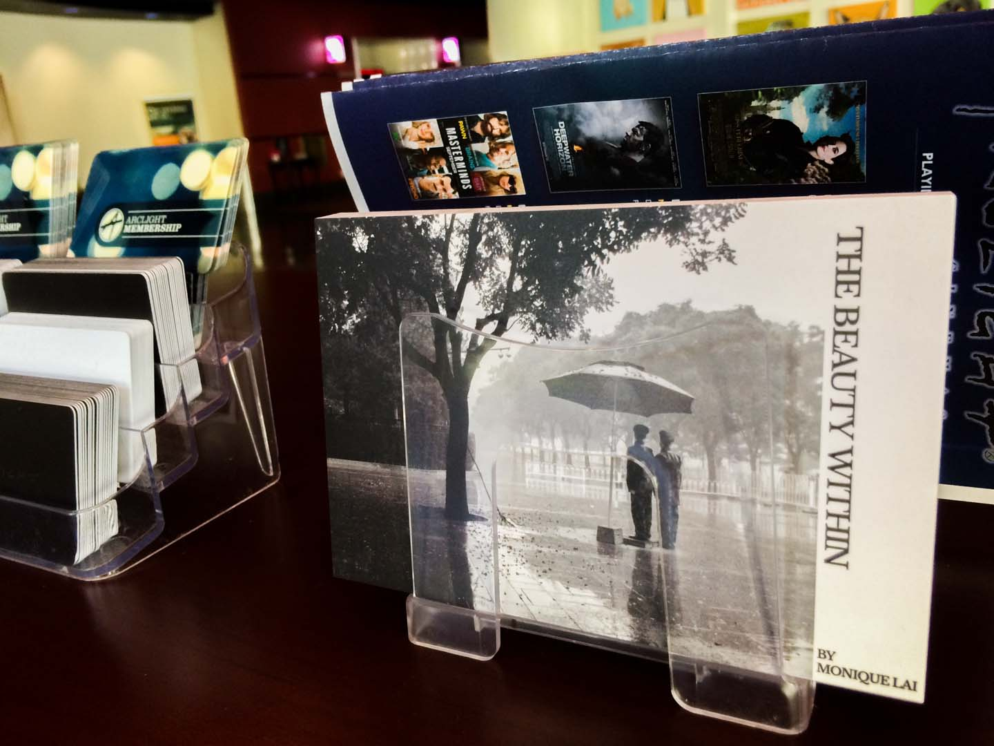 Postcards from 'The Beauty Within' photo exhibition are placed on a table alongside ArcLight membership brochures.