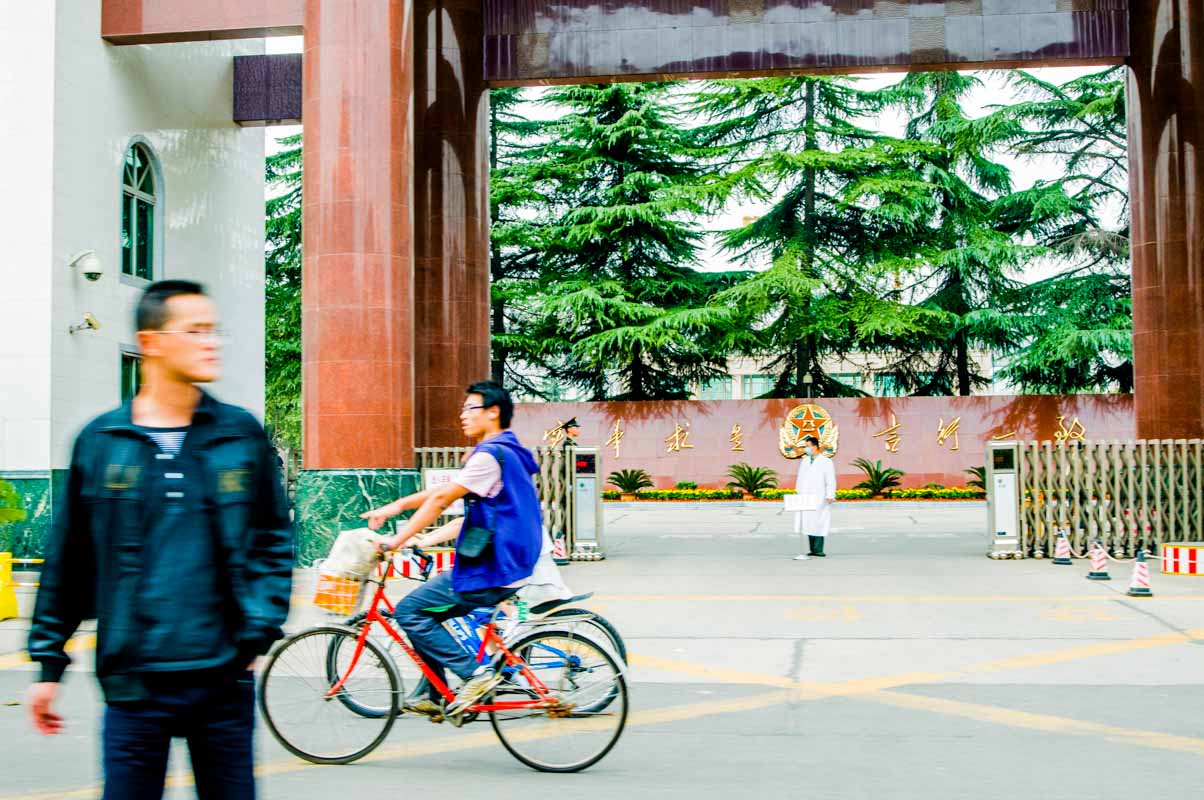 A man waits to safely cross the street while 2 people on bicycles ride behind him out of view. A spectacular view of large pine trees can be seen inside the courtyard of a hospital.