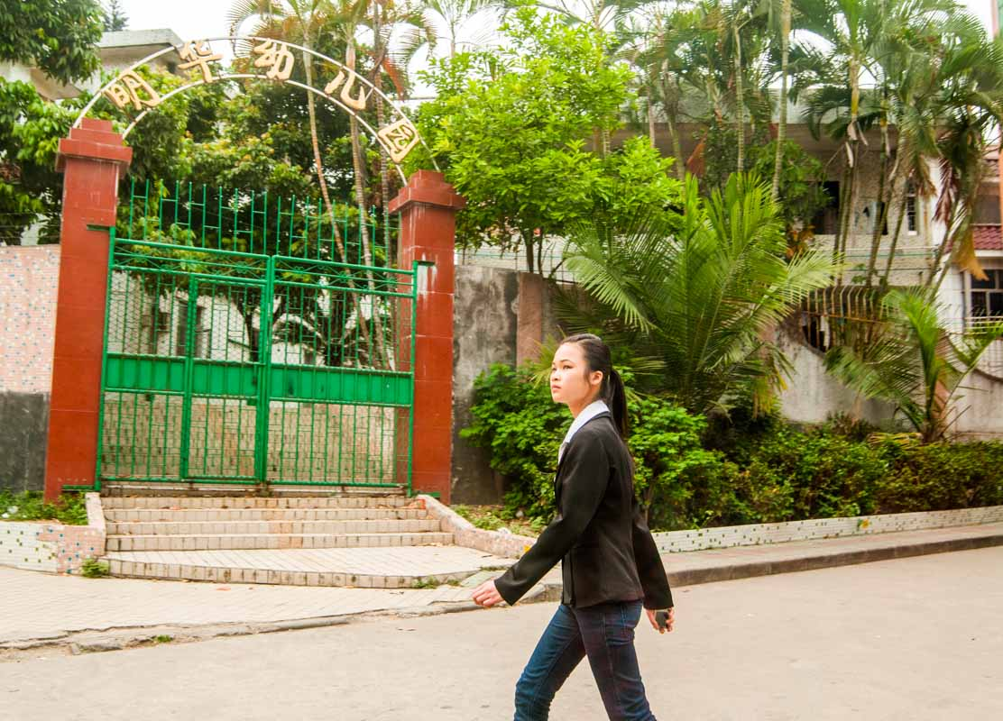 A girl in Shenzhen walks in front of a school holding her mobile phone.
